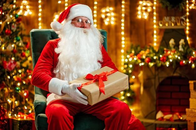 Santa claus holding gift box for children