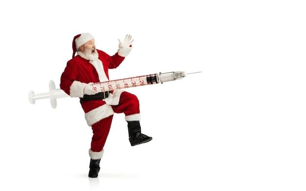 흰색 배경에 격리된 크리스마스 선물처럼 covid에 대한 거대한 백신을 들고 있는 산타클로스. 전통 의상을 입은 남성 모델. 새해, 휴일, 겨울, 전염병, 전염병 개념. 카피스페이스.