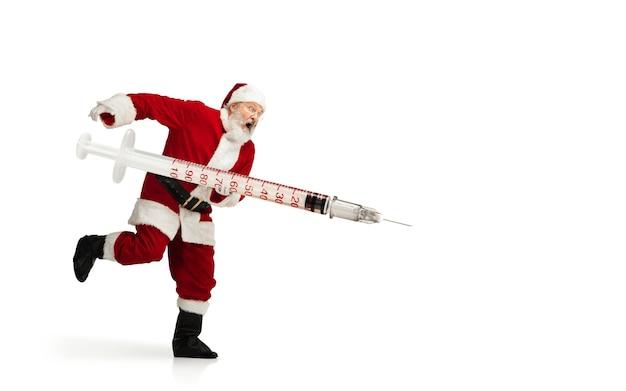 白い背景で隔離のクリスマスプレゼントのようなcovidに対する巨大なワクチンを保持しているサンタクロース。伝統的な衣装の男性モデル。新年、休日、冬、流行、パンデミックの概念。コピースペース。