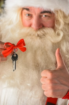 Santa claus holding keys of new house or apartment and thumbs up good mortgage offer concept