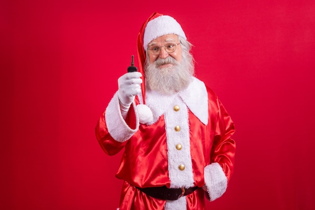 Санта-клаус держит ключи от машины на красном фоне