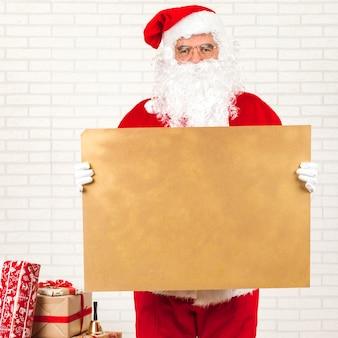 Santa claus holding kraft blank paper