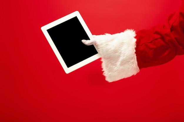 サンタクロースが赤いスタジオの背景にクリスマスの準備ができているラップトップを保持しています。季節、休日、お祝い、ギフトのコンセプト