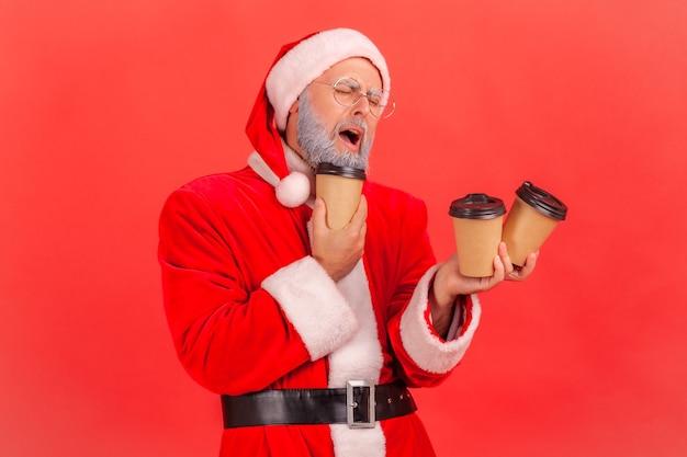 커피와 함께 많은 종이컵을 들고 있는 산타클로스는 많은 에너지를 필요로 합니다.