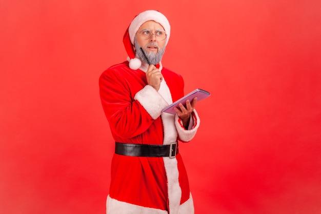 노트북을 손에 들고 있는 산타클로스는 크리스마스 휴일 선물에 대해 생각합니다.