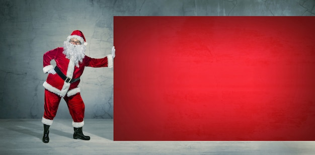 Copyspaceと空白の広告バナーを保持しているサンタクロース。クリスマスのテーマ、販売