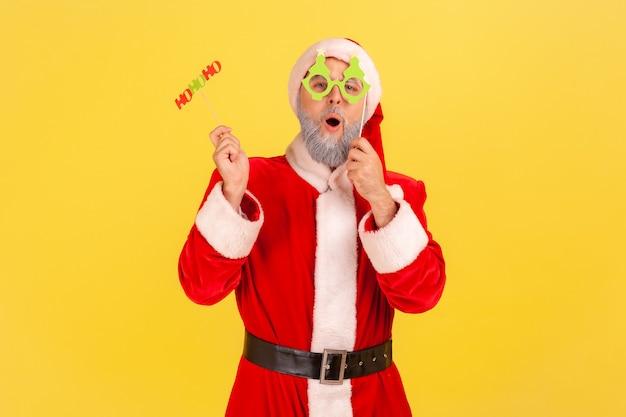 棒に紙のカードを持って、クリスマスを祝い、新年を祝うサンタクロース。