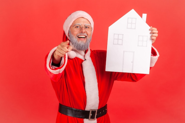 Santa claus holding paper house in hands, pointing to you, offering new flat.