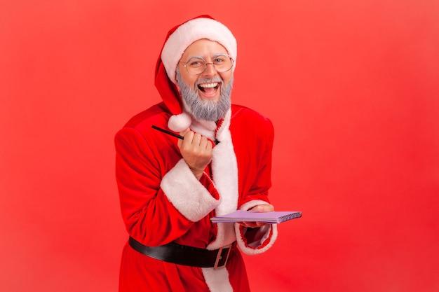 종이 노트북과 펜을 손에 들고 웃고, 카메라를 보고 있는 산타클로스.