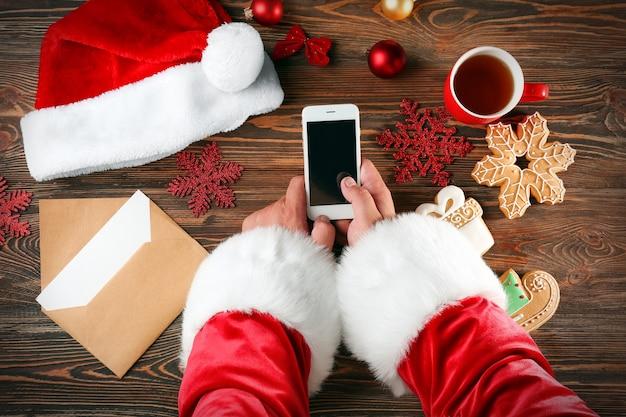 Санта-клаус держит телефон за деревянным столом