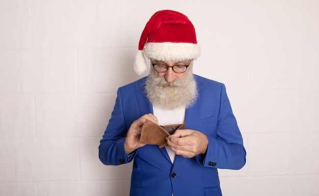 Santa claus holding purse with out money on white background. no money for xmas. new year.