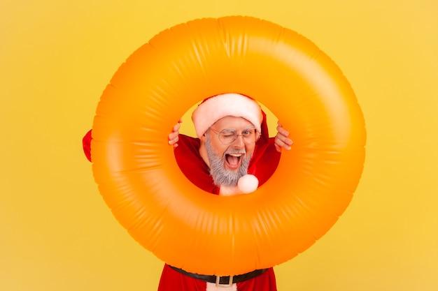 고무 링을 손에 들고 카메라를 보고 윙크하는 산타클로스, 크리스마스 투어.