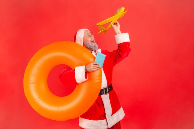 Santa claus holding rubber ring, passport and paper plane, rejoicing future trip.