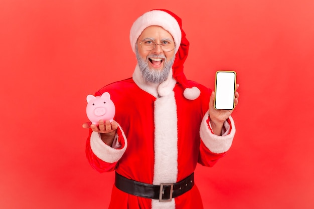 Santa claus holding smart phone with white blank screen and piggy bank, cashback, online wallet.