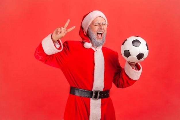 축구공을 손에 들고 카메라에 v 표시를 하고, 윙크하고, 입을 벌린 산타클로스.