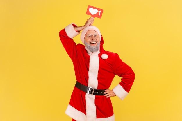 소셜 네트워크를 들고 산타 클로스 심장 처럼 머리 위에 아이콘, 이빨 미소로 카메라를 찾고.