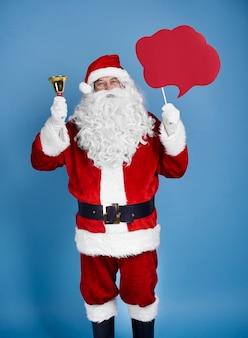Санта-клаус держит речевой пузырь и колокольчик