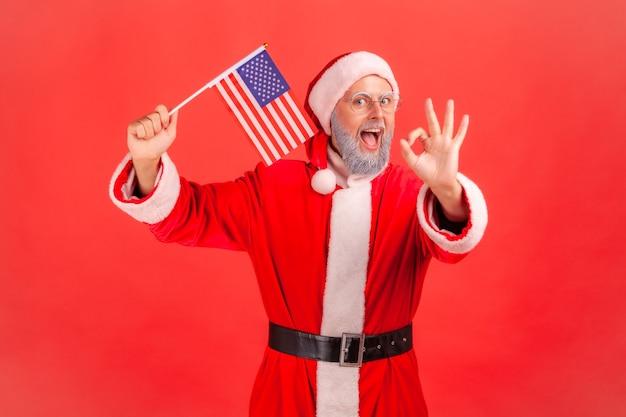 Санта-клаус держит в руках флаг сша и показывает знак хорошо на камеру.