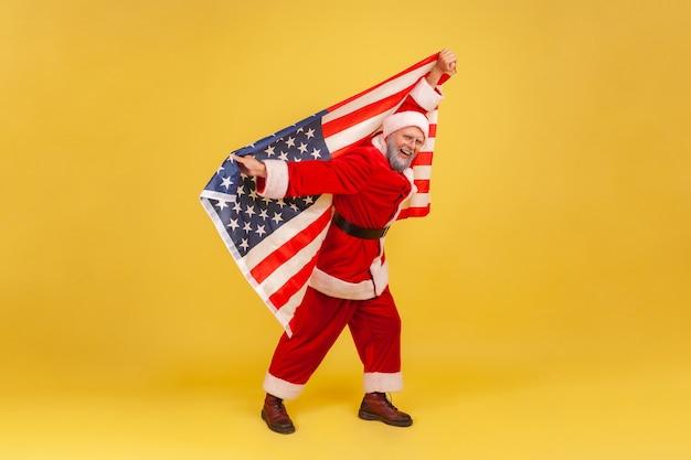 Санта-клаус держит в руках флаг сша, глядя в камеру, делая вид, что летит, празднует новый год.