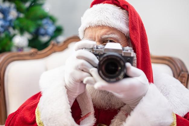 Santa claus holding vintage camera