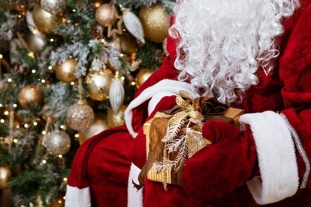 サンタクロースはクリスマスツリーのお祭り気分でミトンで贈り物を保持します