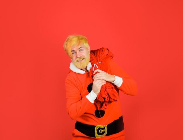 Санта-клаус держит большой подарок санта-клаус с новогодним подарком новогодние подарки новый год с рождеством