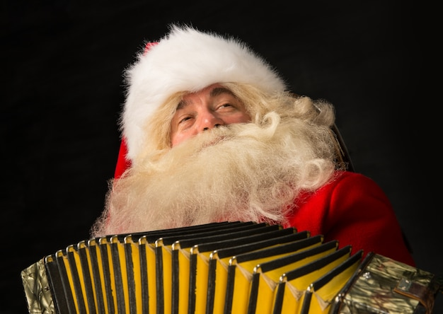 Santa claus at home and playing music on accordion.