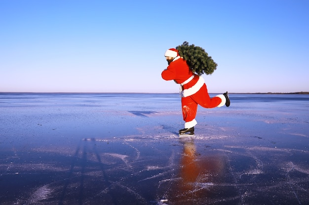 Santa claus on ice skates goes to christmas. santa claus hurries to meet the new year with gifts and christmas tree.