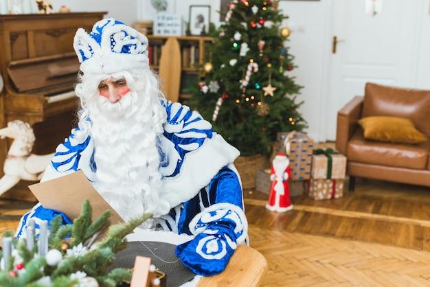 青い毛皮のコートを着たサンタクロースは、クリスマスツリーを背景に子供からの手紙を読みます。