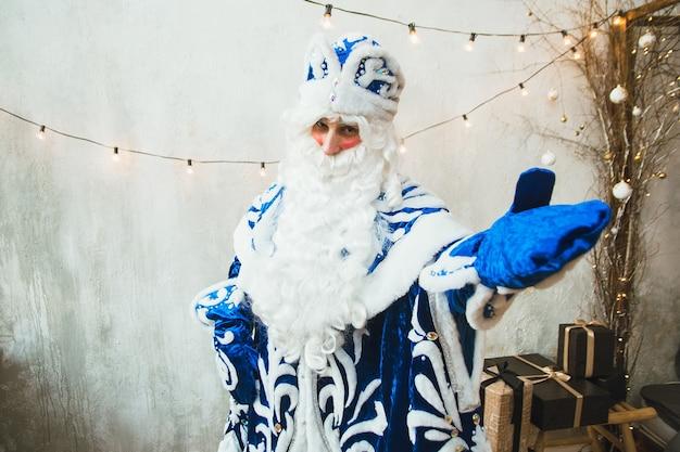 파란색 모피 코트를 입은 산타 클로스는 새해 화환의 배경에 서서 장갑을 낀 손으로 카메라를 가리 킵니다.
