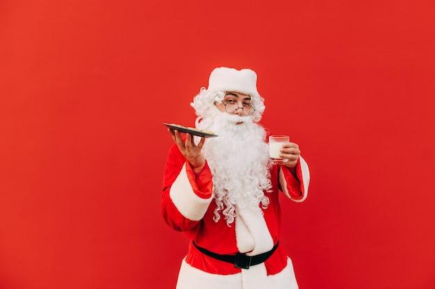 派手な衣装と眼鏡をかけたサンタクロースは、赤い背景の写真のポーズをとり、クッキーと牛乳のグラスが入ったプレートを持っています。