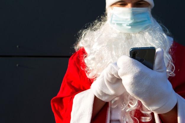 Дед мороз в медицинской маске со смартфоном. онлайн поздравления, заказ услуг на рождество и новый год. социальная дистанция в эпидемии коронавируса, новая реальность. копировать пространство