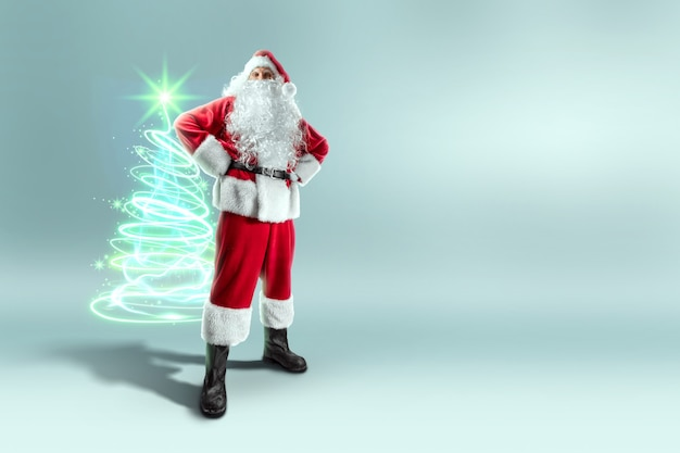 ネオンのクリスマスツリーと赤いスーツを着たサンタクロース