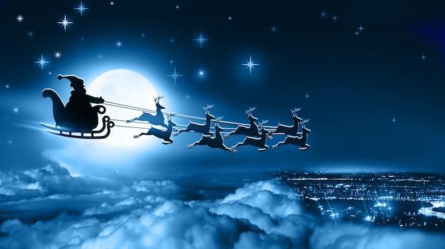 썰매와 순록 썰매를 탄 산타클로스는 밤 겨울 흐린 하늘에 보름달을 배경으로 지구 위로 날아갑니다.