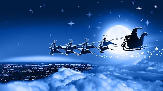 썰매를 탄 산타클로스는 밤 겨울 흐린 하늘에 보름달을 배경으로 지구 위로 날아간다