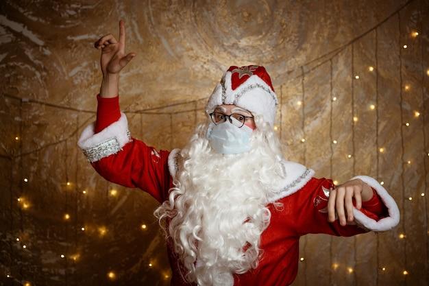 안경과 마스크를 쓴 산타클로스는 손으로 벽 배경에 손으로 제스처를 보여줍니다.