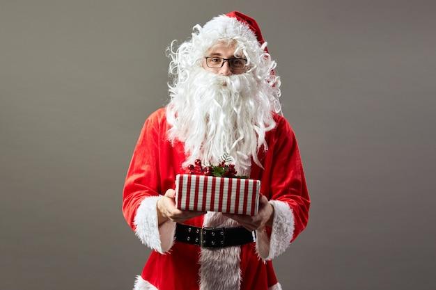 안경을 쓴 산타클로스는 회색 배경에 크리스마스 선물을 손에 들고 있습니다. .
