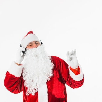 Santa Claus in glasses listening to music with headphones