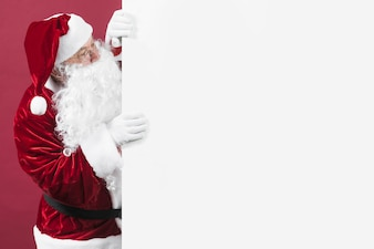 Santa Claus in glasses looking out of white wall