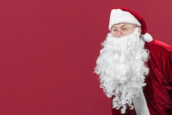 Santa Claus in glasses peeping looking on red background