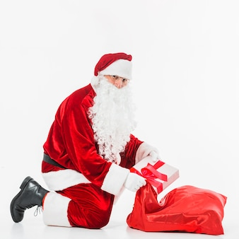 Santa Claus in glasses putting gift box in sack