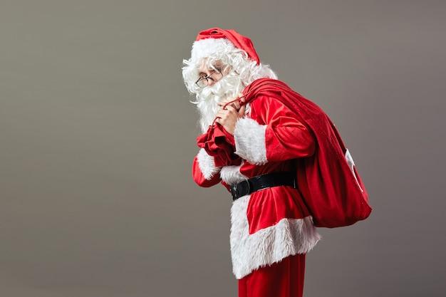 Санта-клаус в очках стоит с сумкой с рождественскими подарками на спине на сером фоне.
