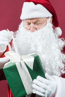 Santa Claus in glasses with green gift box in hands