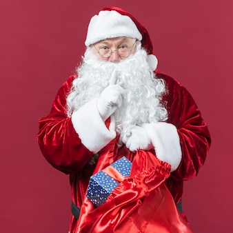 Santa Claus in glasses with sack of gifts showing secret gesture