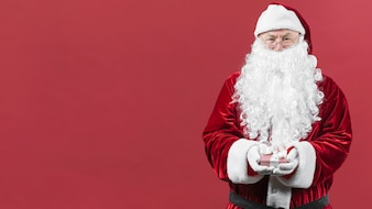 Santa Claus in hat holding small gift box