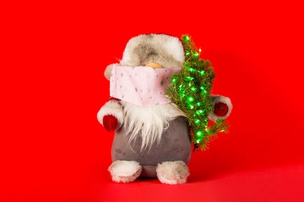 Санта-клаус в медицинской маске с елкой на красном