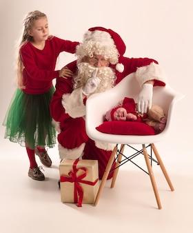 小さな女の子と白で隔離の赤ちゃんと赤い衣装でサンタクロース
