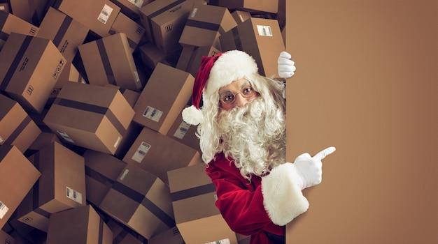 산타 클로스는 배경에 준비된 패키지와 함께 크리스마스 선물을위한 빈 공간을 나타냅니다.