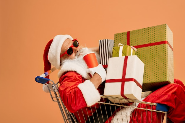 Santa claus inside shopping cart with lots of gift boxes
