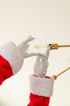 サンタクロースが電球を交換しています